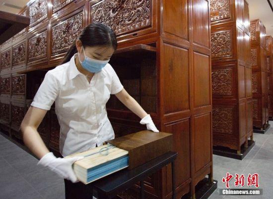 8月17日,甘肃省兰州市天庆博物馆的工作人员在整理该馆收藏的文渊阁版《四库全书》影印本。中新社记者 高展 摄