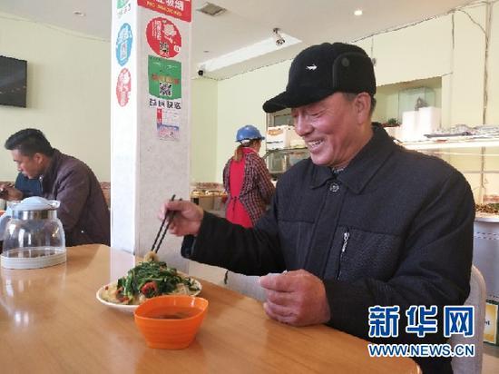 图为领取到免费午餐的张彦祥老人。