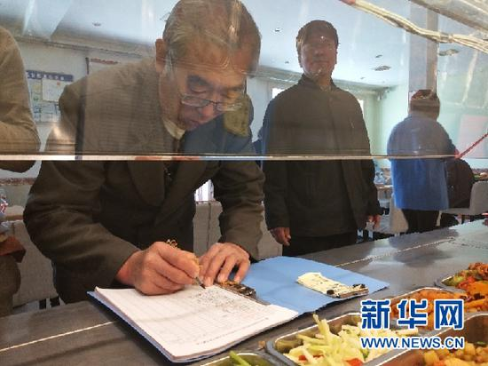 图为一名老人登记领取免费营养午餐。