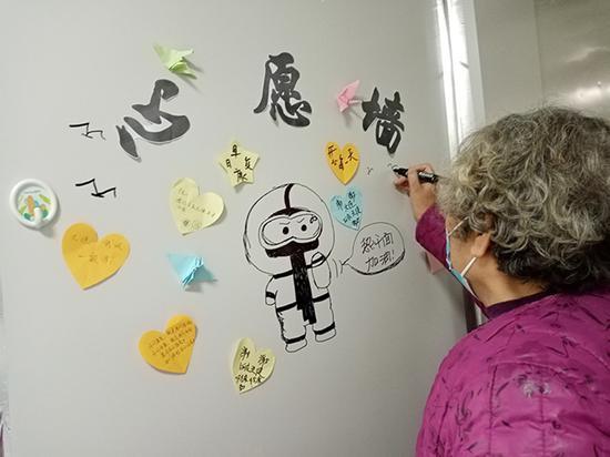 患者在手绘心愿墙上画海鸥写心愿。