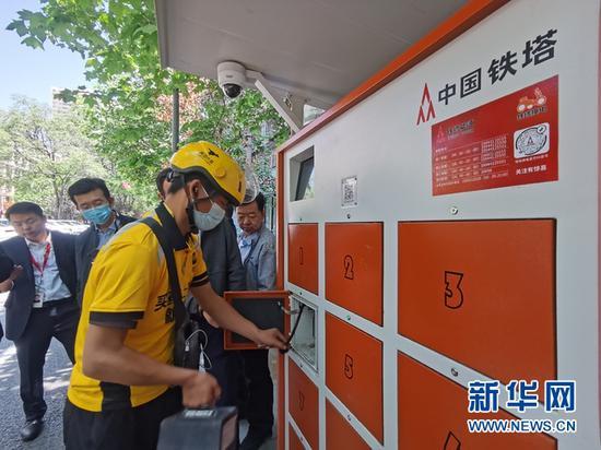 """外卖骑手通过甘肃铁塔""""5G+智慧能源""""换电柜完成快速换电。甘肃铁塔供图"""