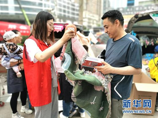 志愿者正在为市民展示爱心义卖物品。新华网发(宋昱静 摄)