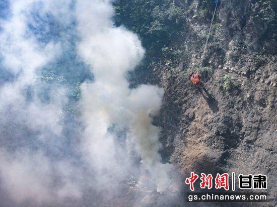 图为指战员在扑灭悬崖烟点。