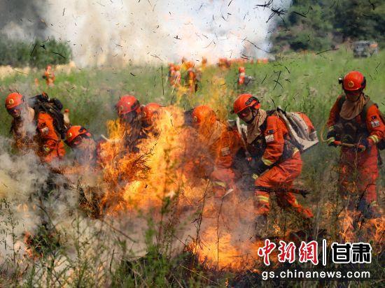 图为指战员在采用一点突破战术扑打火线。