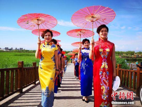 6月24日,甘肃张掖市的旗袍爱好者在张掖市国家湿地公园走秀展示旗袍之美。吴学珍 摄