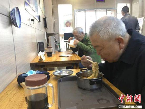 """近日,甘肃省餐饮服务单位全面恢复堂食就餐,顾客隔凳(椅)就座,间隔保持在1米以上。图为兰州民众自带碗到牛肉面馆""""吃牛大""""。 张婧 摄"""