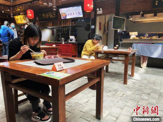 图为兰州中心食客单人单桌、同向进行就餐。 高康迪 摄