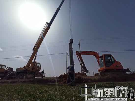 图为电力工人力们正在开展运杆、挖坑、栽杆、制作拉线