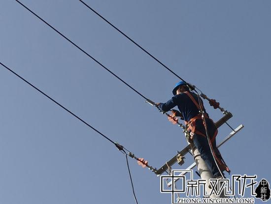 图为电力工人力检修线路