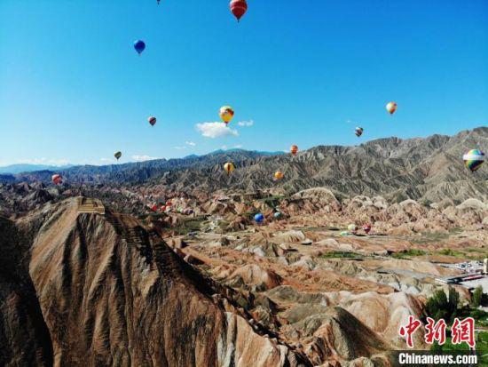 2019年7月19日,来自中国各地的100名热气球运动员驾乘100具热气球,从七彩丹霞景区3处起降点同时起飞,飞越整个景区,上演了一场热气球与七彩丹霞的唯美邂逅。(资料图) 杨艳敏 摄