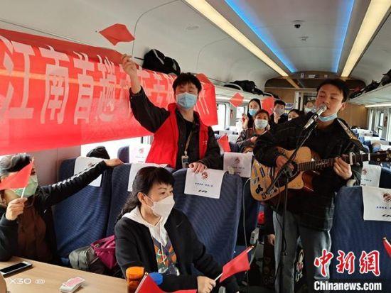4月18日,甘肃省今年首趟省内游旅游动车专列在兰州火车站发车开往陇南,游客在动车组专列上展示才艺。 张天合 摄