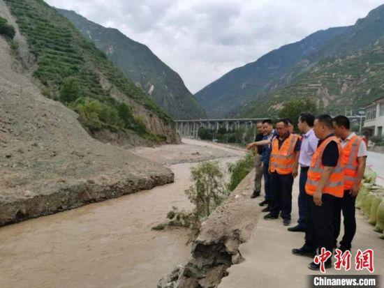 专家组在G212线宕昌县境内查看滑坡阻塞河道、冲毁路基情况。