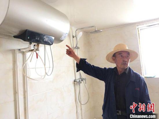 图为刘向信展示自家安装的热水器。
