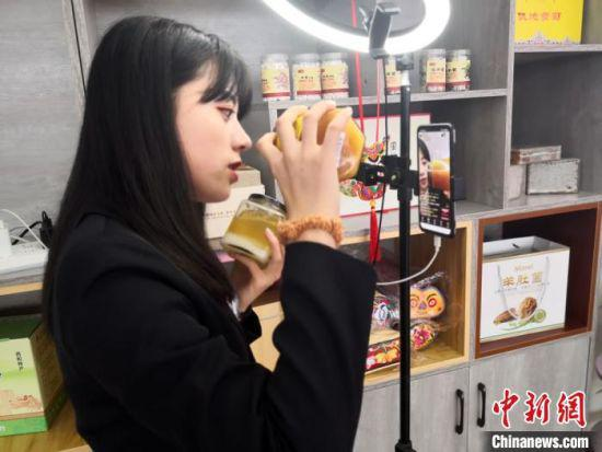 """图为西和县消费扶贫直销店工作人员正进行""""直播带货""""促销活动。"""