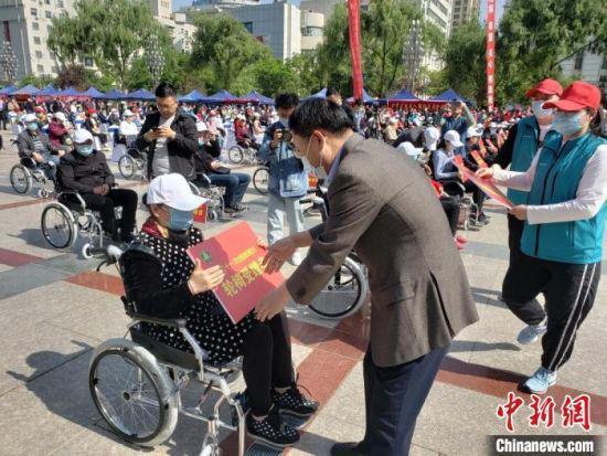 """5月16日,兰州市第三十一次""""全国助残日""""系列活动举办。图为给残障人士捐赠轮椅。 闫姣 摄"""