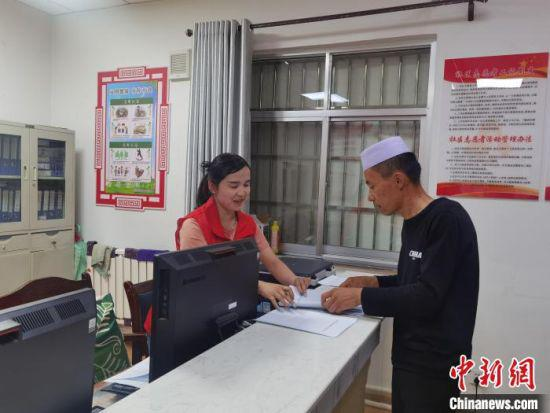 图为武威凉州区东关街寺巷子社区工作人员为少数民族居民办理业务。 崔琳 摄