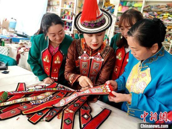 图为裕固族服饰非遗传承人(左二)教授裕固族农牧民服饰刺绣。 史静静 摄