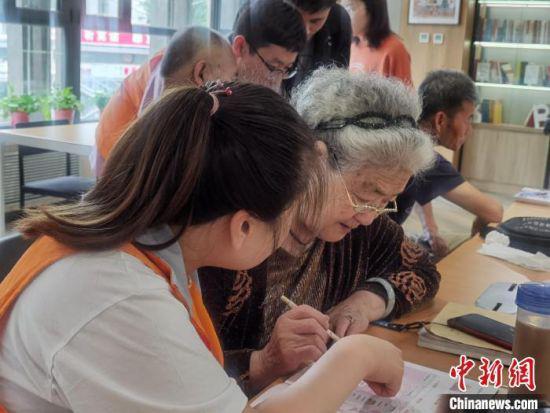图为84岁老人张凤英在社工指导下学习使用智能手机。 崔琳 摄