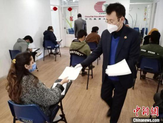 2021年,中巴教育文化中心考点HSK(汉语水平考试)考试现场,马斌(右一)给考生发试卷。(资料图) 受访者供图