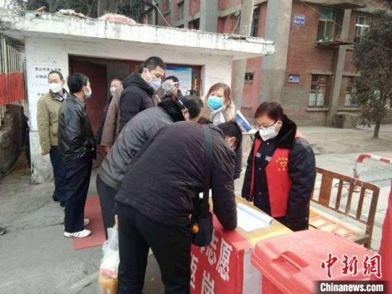 图为姜波(穿红马甲)和同事在防疫卡口点值守。(资料图) 受访人供图