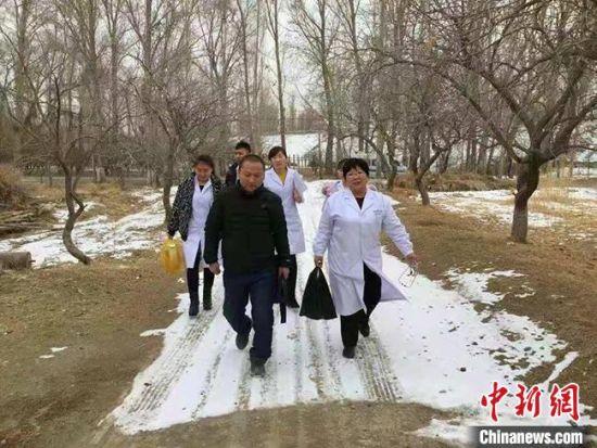 """图为冯世霞(右一)带领医务人员前往""""健康扶贫入户""""的路上。(资料图) 受访者供图"""