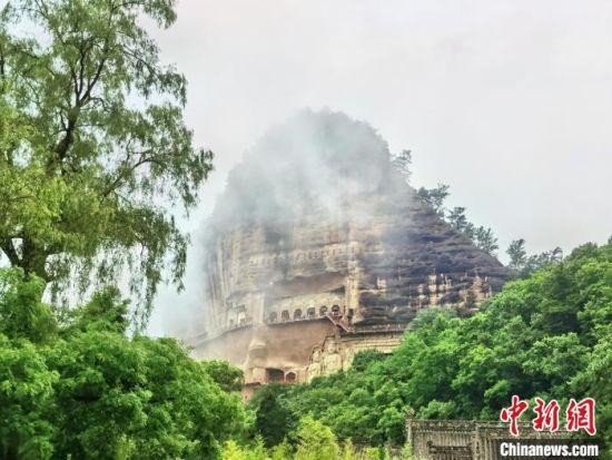 麦积山石窟是中国四大石窟之一,以精美绝伦的泥塑壁画闻名于世,细雨绵绵下的麦积山石窟江南风韵十足。 张婧 摄
