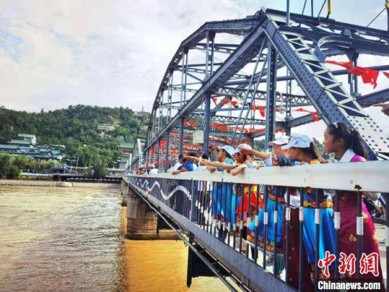 图为7月17日,来自甘肃甘南藏族自治州的青少年游览兰州百年中山铁桥。 史静静 摄