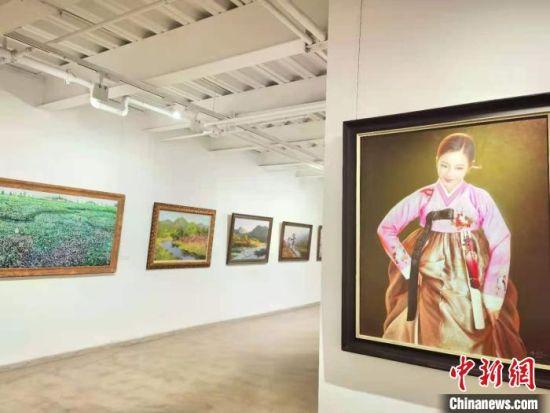 """图为7月27日,""""惟美无界—当代朝鲜油画名家精品展""""正在兰州展出,吸引民众驻足欣赏。 史静静 摄"""