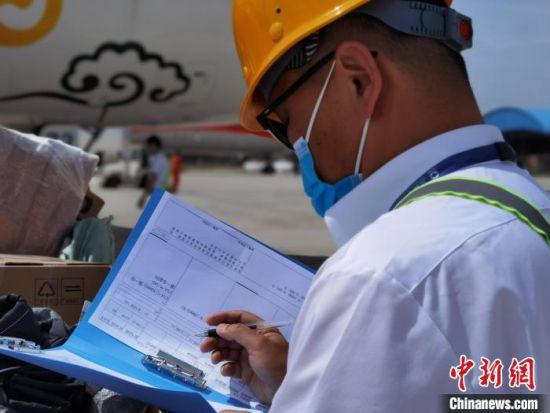 近日,兰州中川机场内,负责航班货物装卸的工人在高温下工作。图为对照行李单。 杨娜 摄