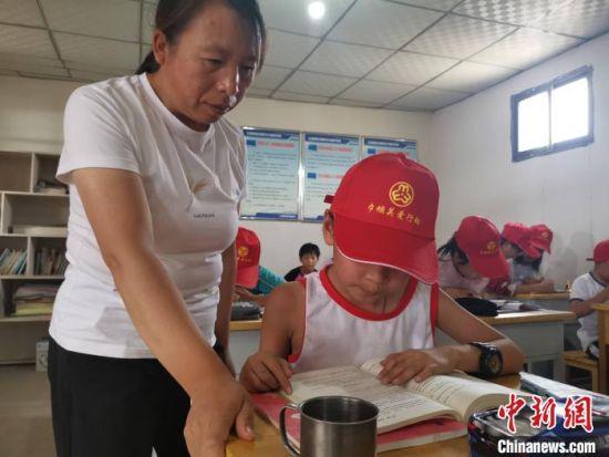 图为王玉红指导留守儿童做作业。 受访者供图
