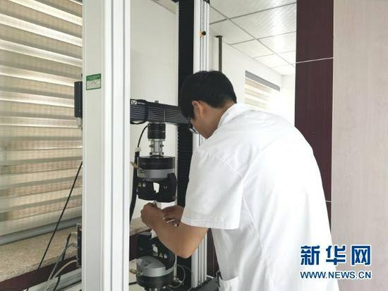 检测人员正在进行防护服的断裂强力和伸长率测试。(李昊 摄)
