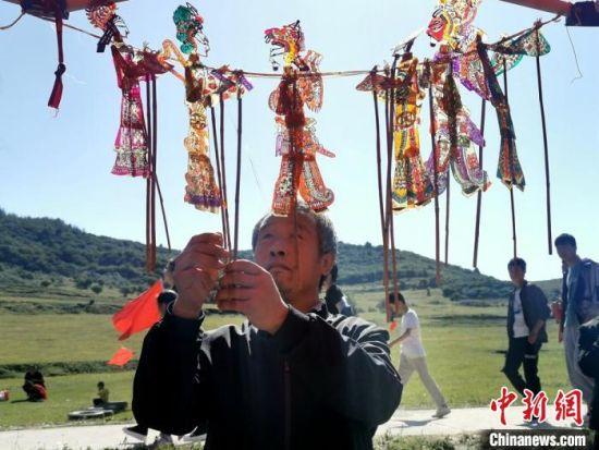 图为村民展示皮影。 秦亭镇政府供图