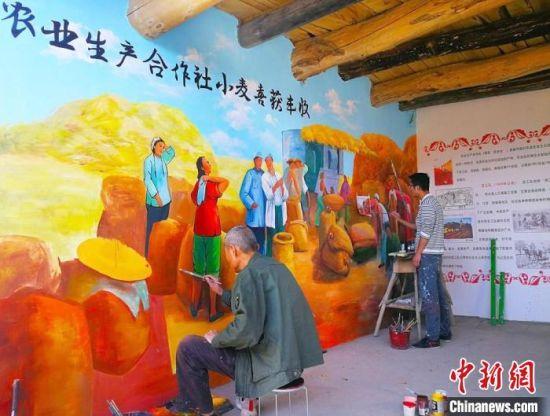 """图为甘肃境内手艺人描绘""""红色记忆墙""""。(资料图) 高展 摄"""