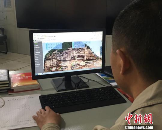 近年来,麦积山石窟艺术研究人员运用物联网技术和传感技术,创建风险监测及提前预警的麦积山石窟监测预警体系,进行数据分析对石窟加以保护。图为胡军舰通过预警体系进行数据监测。 张婧 摄