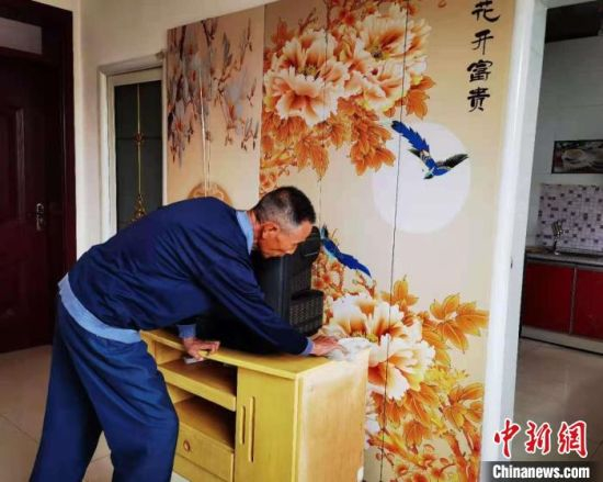 图为村民陈同林每天的日常生活,拿着抹布擦拭新家的桌子,打扫地板,再擦擦厕所的水箱。 史静静 摄