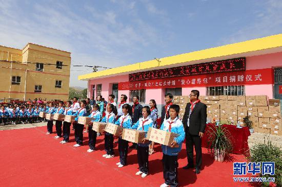 爱心人士为新营小学的贫困儿童捐赠价值10万元的婴幼儿配方奶粉。 信江 摄