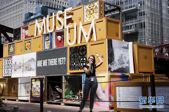 8月23日,在美国芝加哥,一名志愿者向游客介绍浮动博物馆的创作意图。
