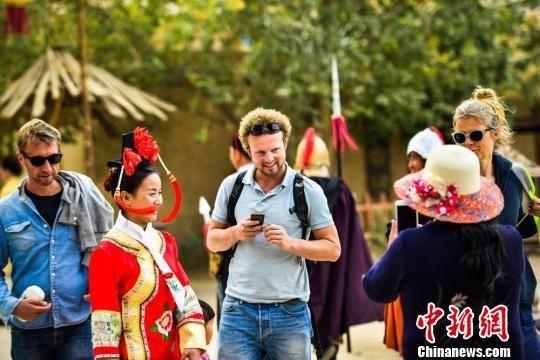 10月5日,中外游客在敦煌古城观光游览。 王斌银 摄