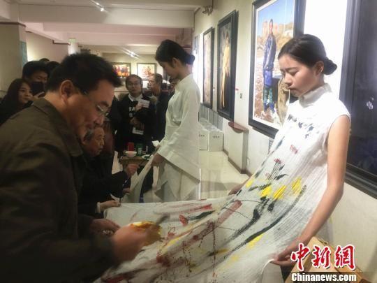 10月18日下午,王秀章携手五名甘肃籍画家在模特服装上手绘,创作了一系列含有中国元素的的画作。 史静静 摄