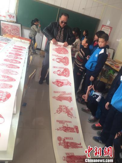 图为学生们围观、学卢建坤的作品。 崔琳 摄