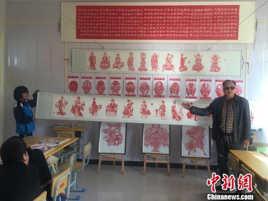 图为卢建坤介绍刀刻作品《金陵十二衩》。 崔琳 摄