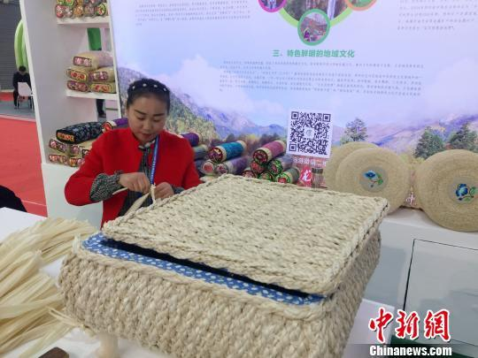 连日来,甘肃西和县农家女何芳在陇南市向民众展示玉米皮编织技巧。 徐雪 摄