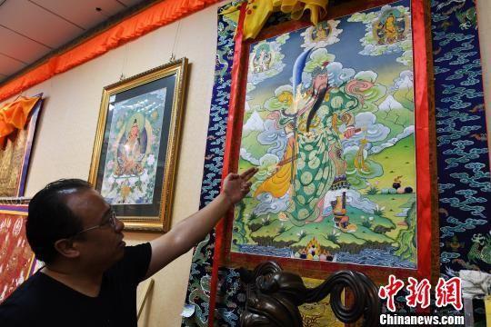 图为藏族唐卡画师夏吾多杰介绍唐卡作品。 杨艳敏 摄