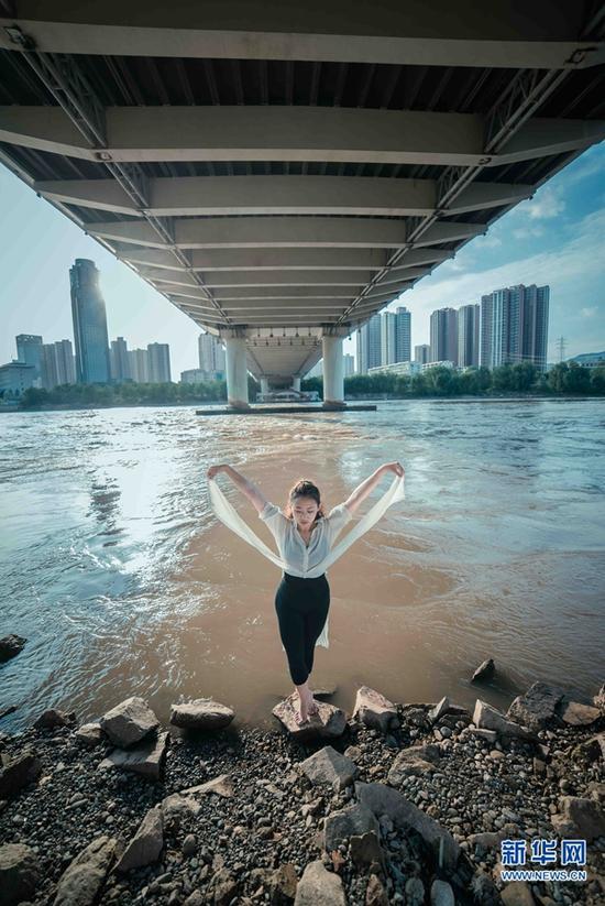 桥下,是滚滚而去的黄河;还有,一个人的舞者。城市舞者郑希夷在黄河岸边舞蹈。
