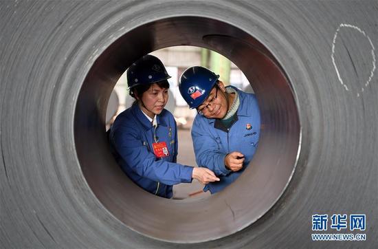在甘肃酒钢集团宏兴钢铁股份有限公司碳钢薄板厂,王云平(左)和同事一起抽检成品钢卷(11月1日摄)。