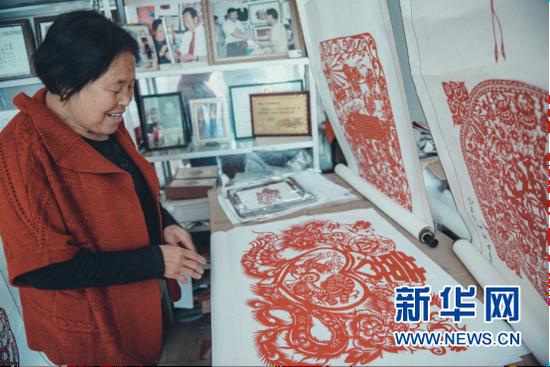 雪秀梅展示自己的剪纸作品。