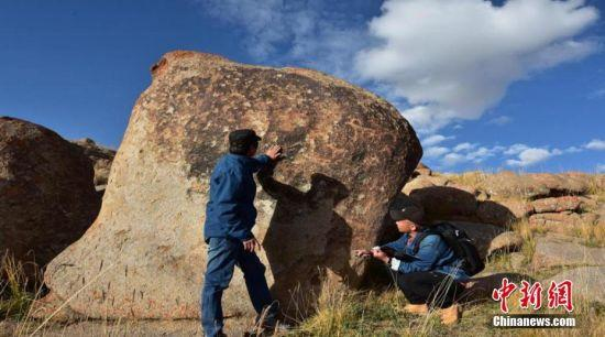 图为文物工作者实地普查登记盐池湾尧勒特岩画。 朱蕊 摄