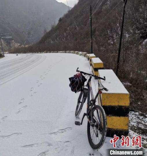 苗兵经过山路休息时,给靠在路边的自行车拍了张照片。自行车把上挂着的是馍馍和泡面 受访者供图