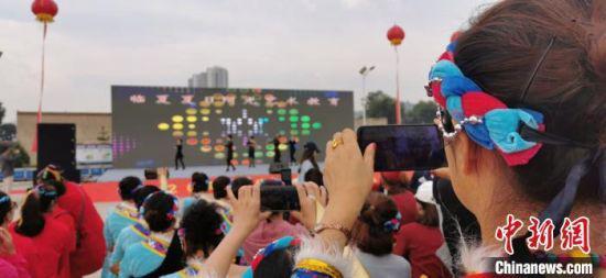 9月初,甘肃临夏州临夏市举办广场舞大赛展演。图为舞蹈演员拍摄记录精彩瞬间。