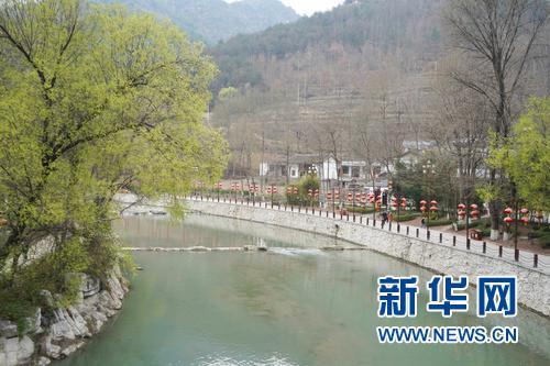 3月24日,游客在甘肃省陇南市康县花桥村河岸边游览。 新华社发(郎兵兵 摄)